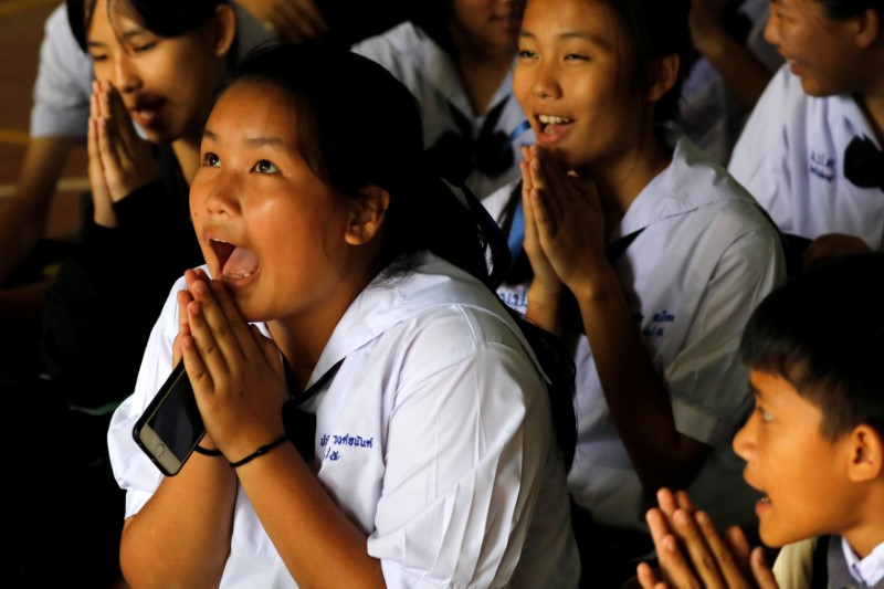 Classmates pray after their teacher announced some of the 12 schoolboys trapped inside a flooded cave, have been rescued, at Mae Sai Prasitsart school, in the northern province of Chiang Rai