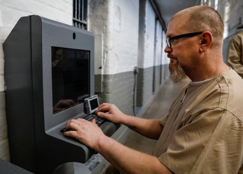 Inmate Steven Goff connects his JPay tablet device to a kiosk inside the East Jersey State Prison in Rahway, New Jersey