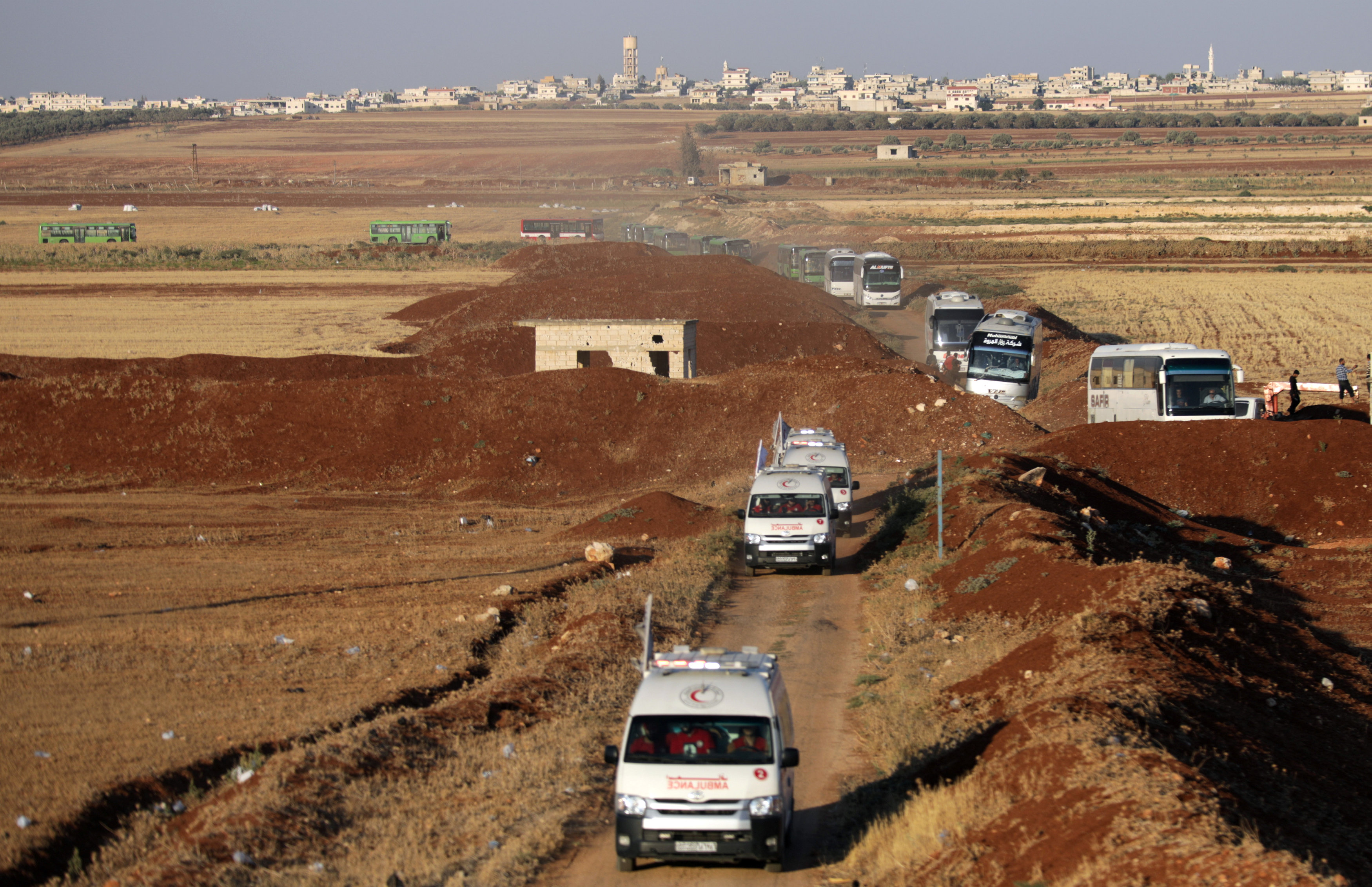 Ambulances and buses are seen near villages of al-Foua and Kefraya