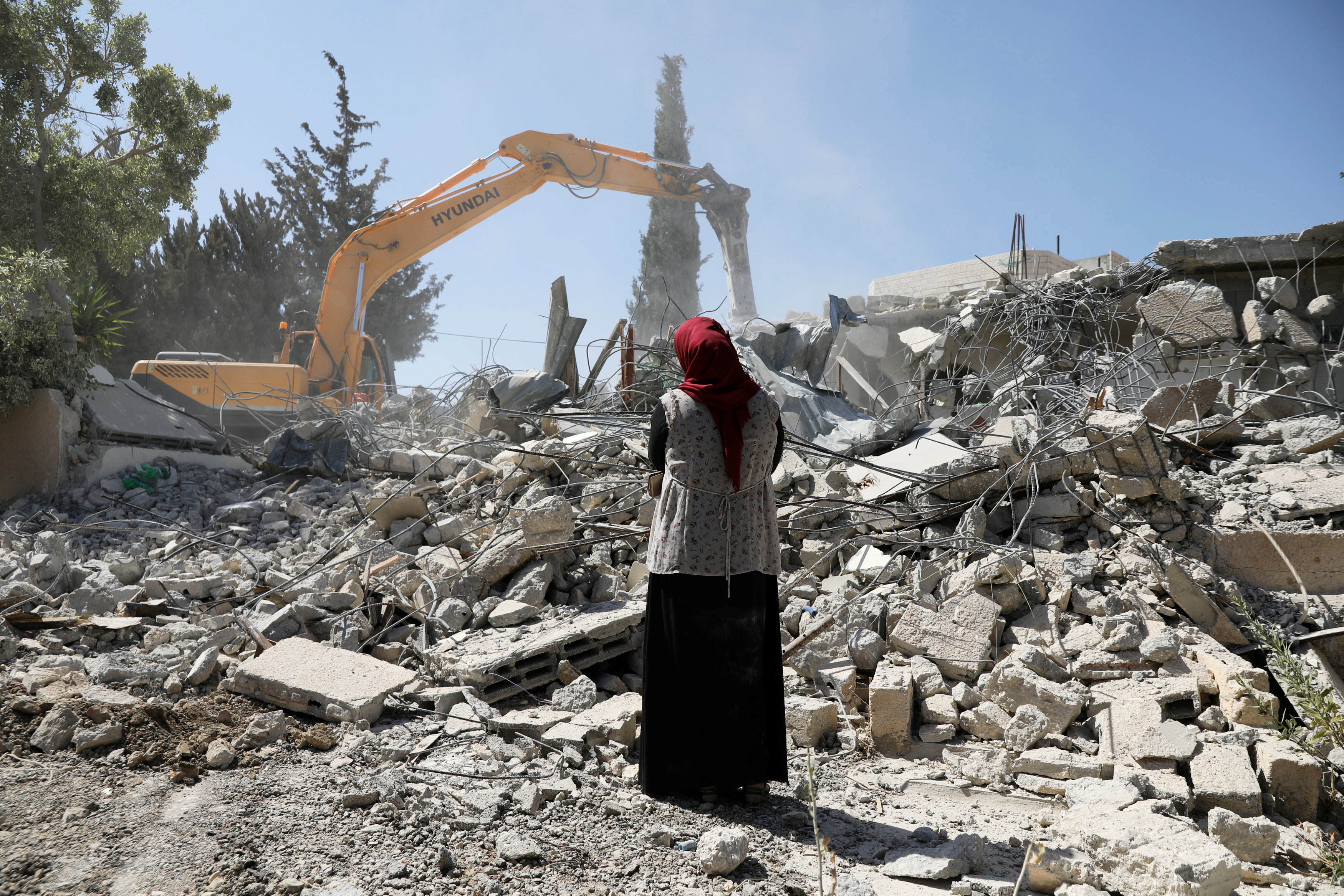 Fawzia stands on the ruins of her house, after her Palestinian ex-husband demolished the dwelling to not face the prospect of Israeli settlers moving in after he lost a land ownership case in Israeli courts