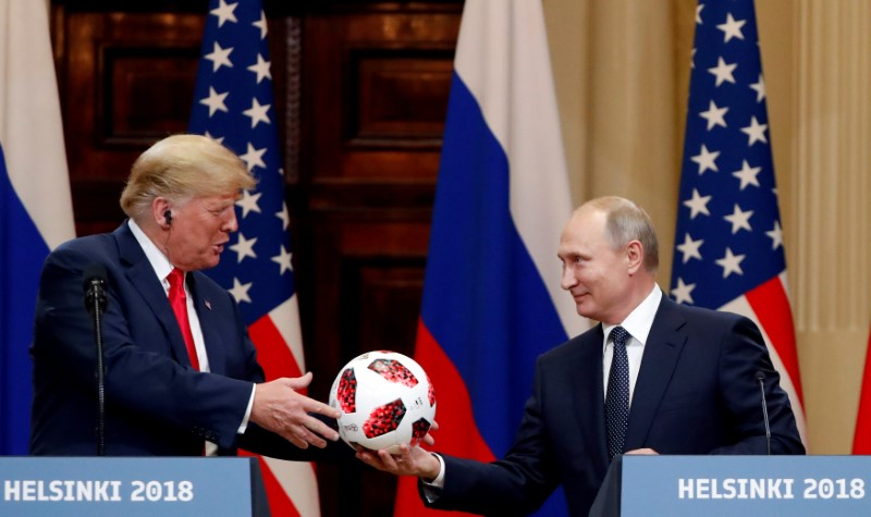FILE PHOTO: U.S. President Donald Trump receives a football from Russian President Vladimir Putin as they hold a joint news conference after their meeting in Helsinki