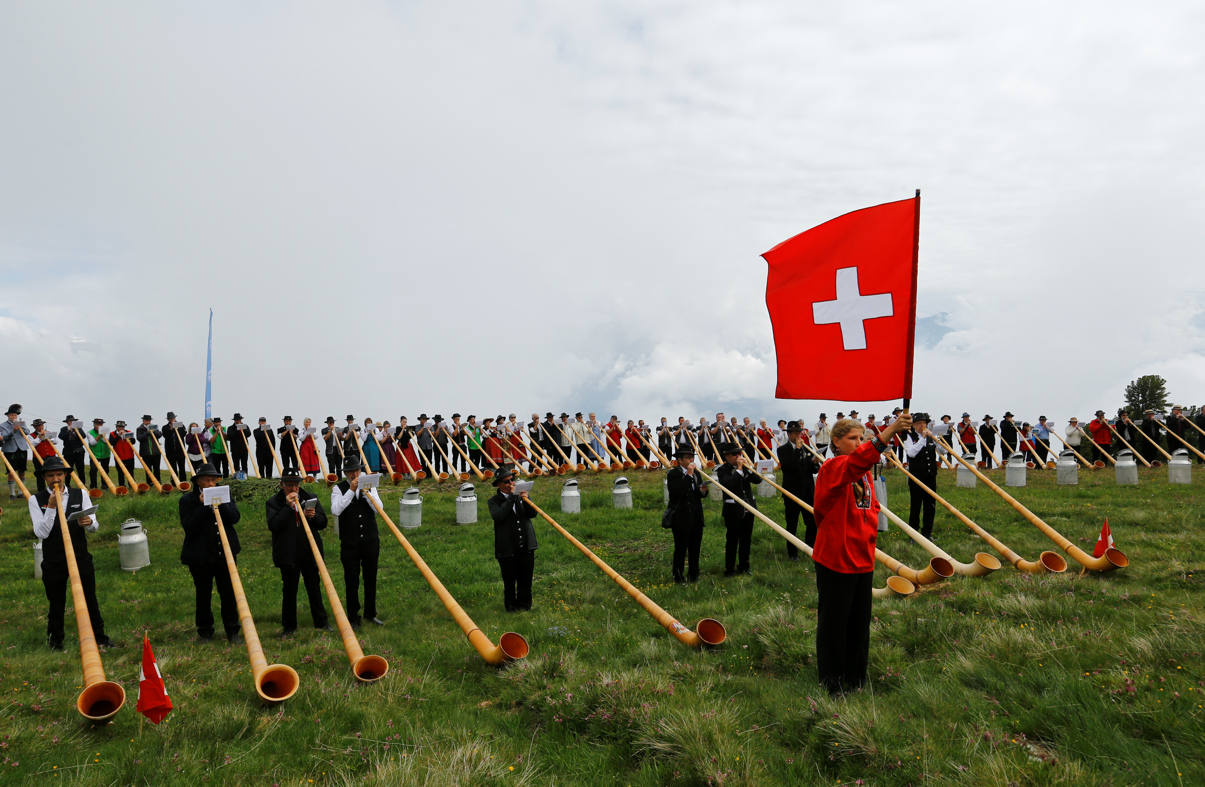 A flag thrower and alphorn blowers perform on the last day of the Alphorn International Festival on the alp of Tracouet in Nendaz