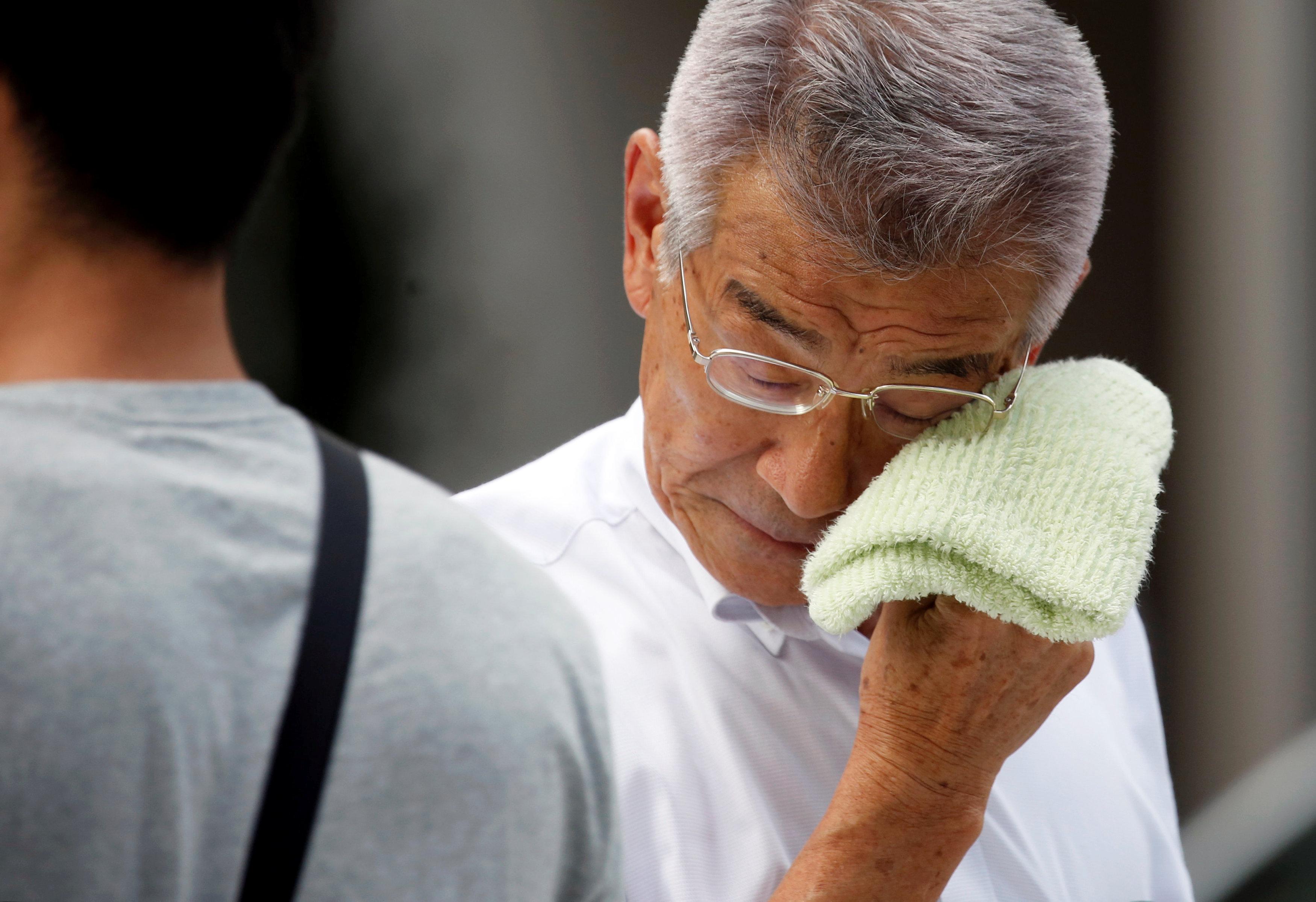 Japan heatwave - man wipes sweat off his face