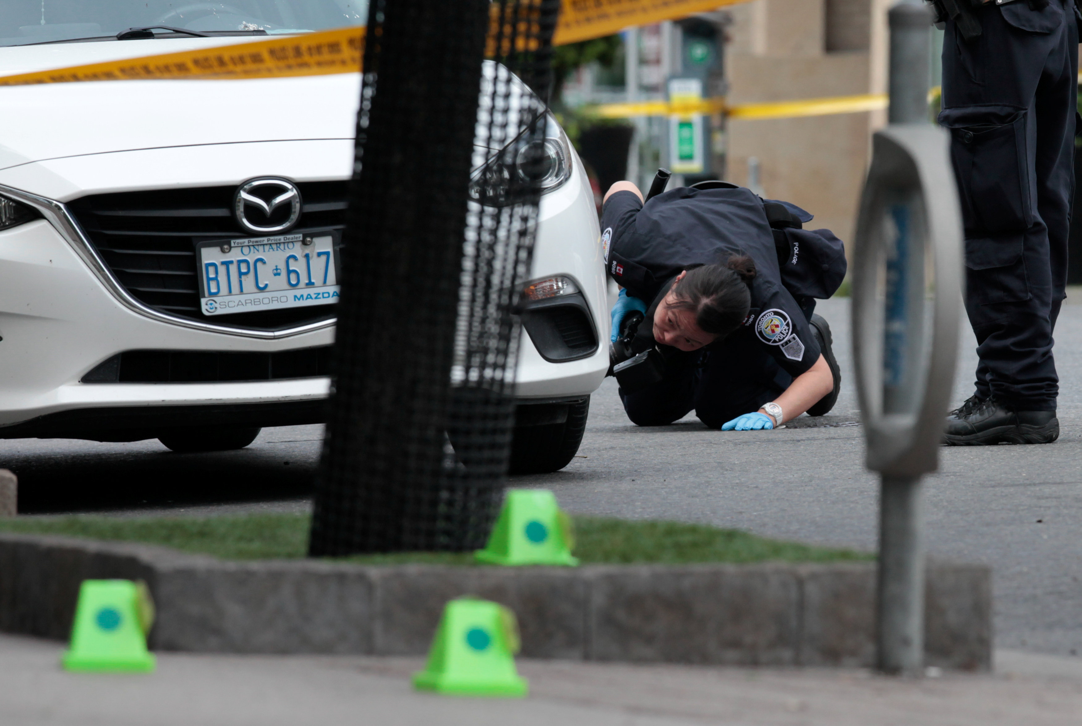 A police officer looks for evidence under a car while investigating a mass shooting in Toronto