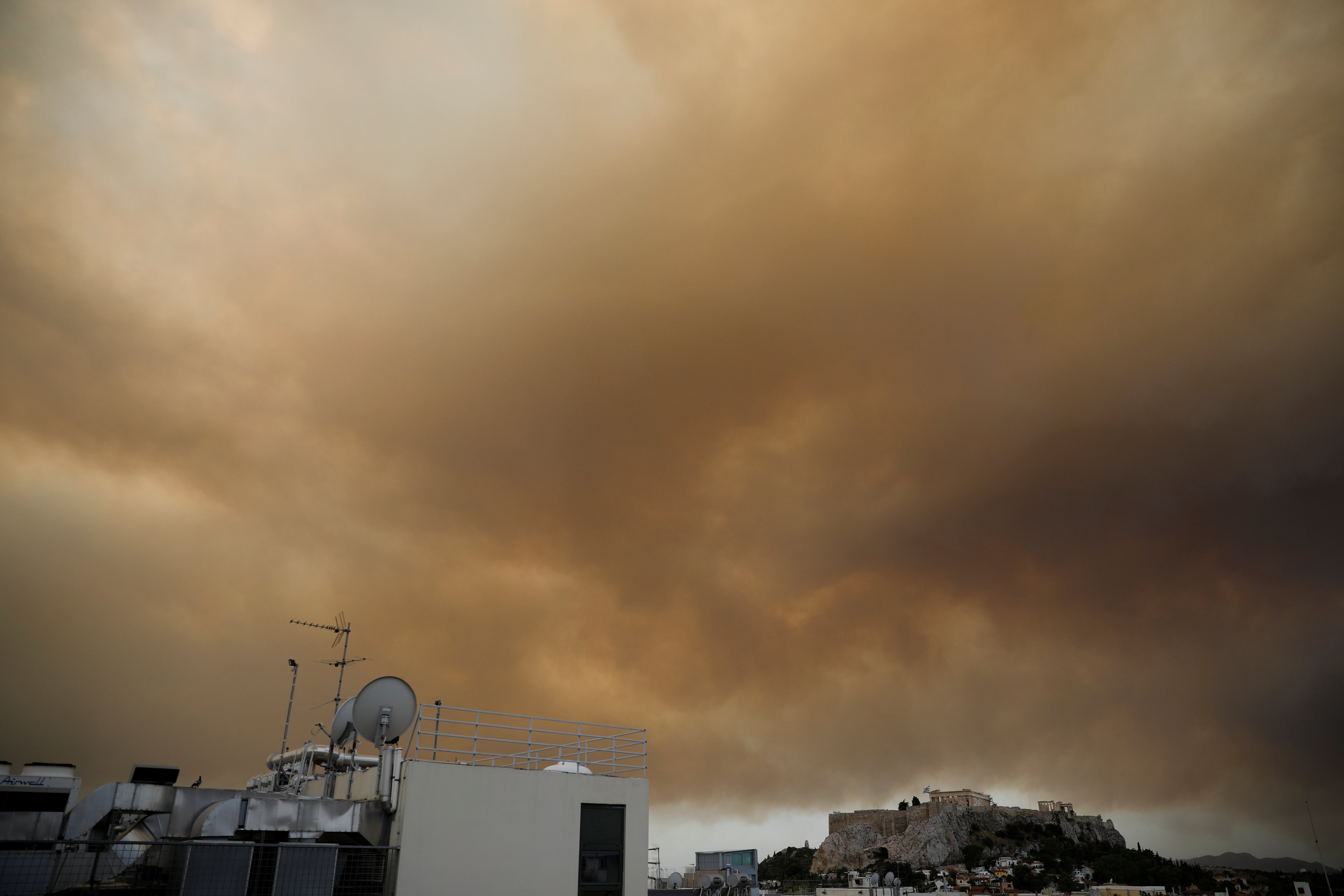 Smoke from a wildfire burning outside Athens is seen over the Parthenon temple atop the Acropolis hill in Athens