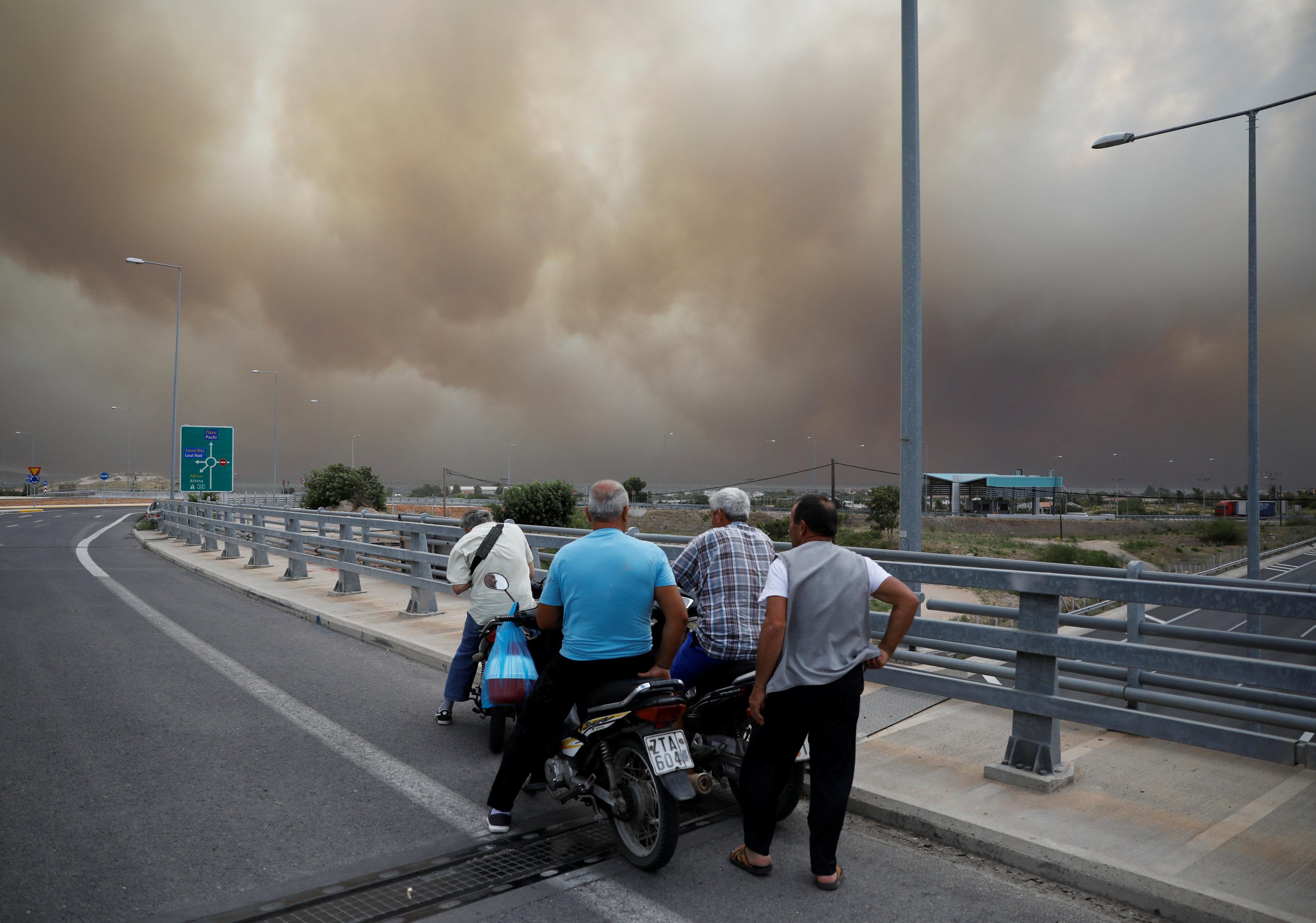 People look at smoke as a wildfire burns in Kineta