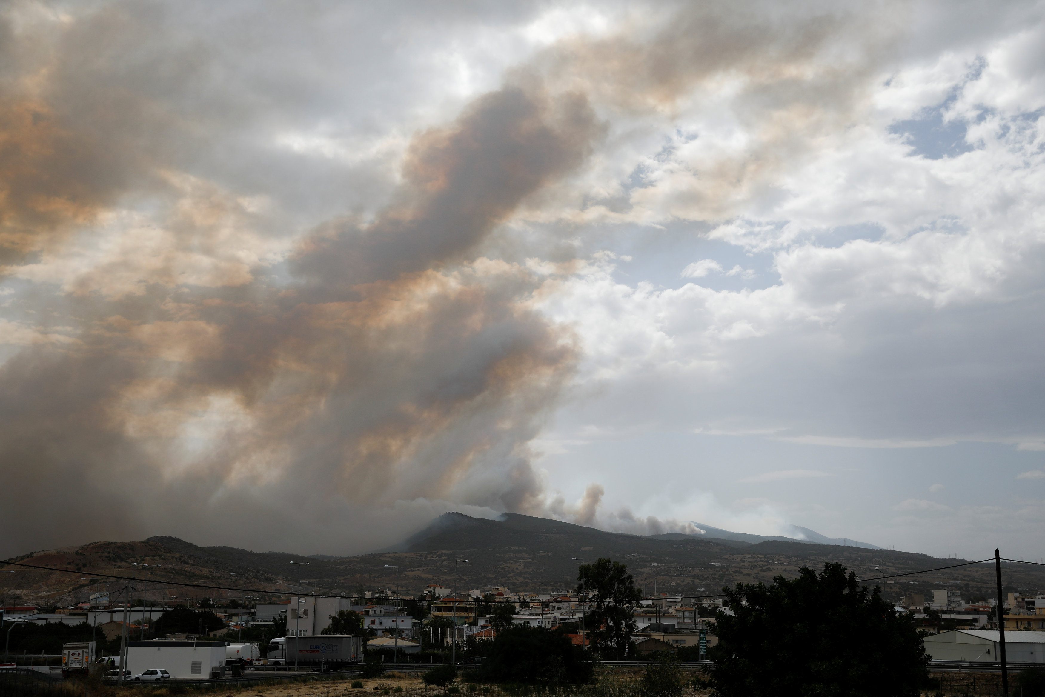 A village is seen amid smoke as a wildfire burns in Kineta