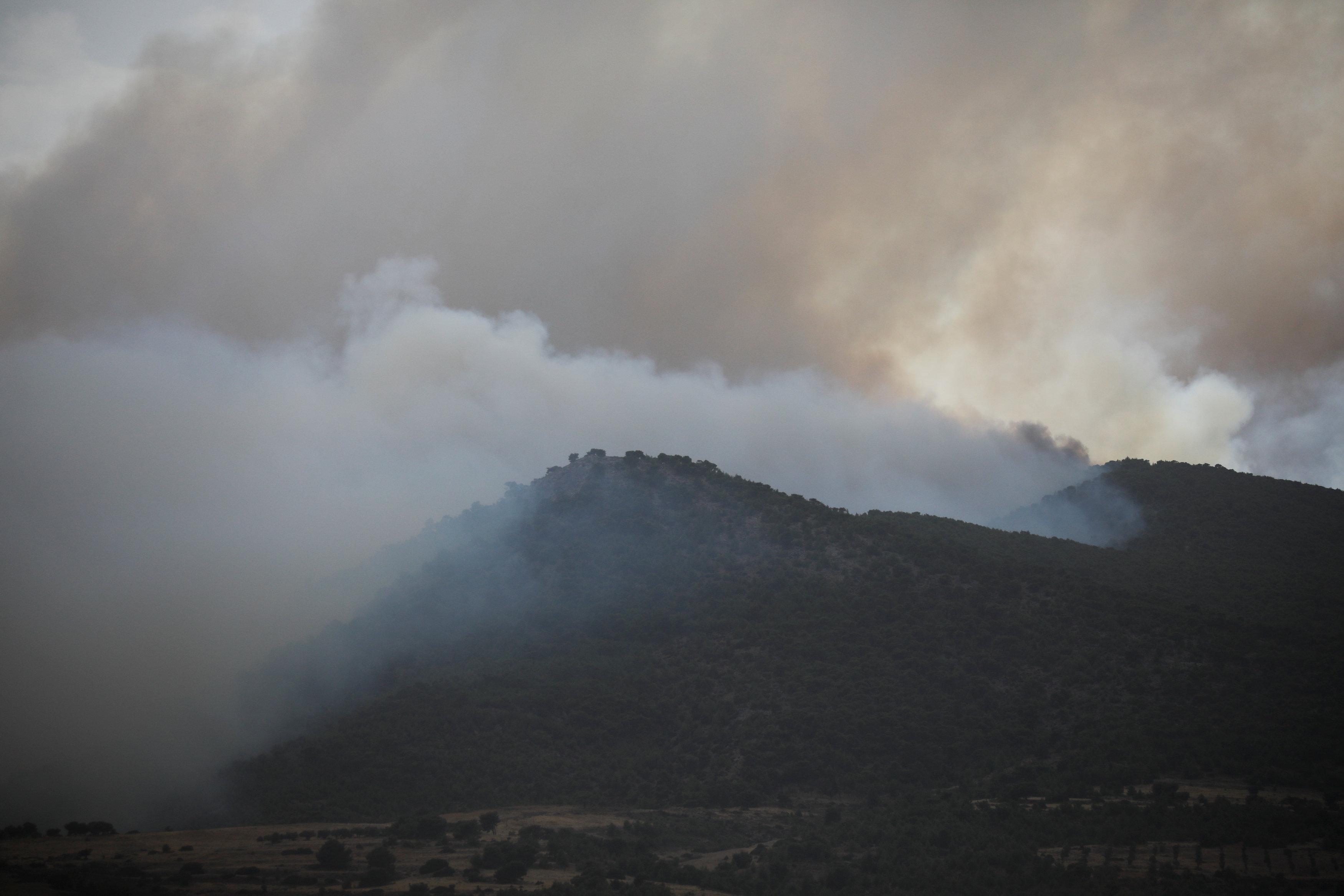 Smoke is seen as a wildfire burns in Kineta