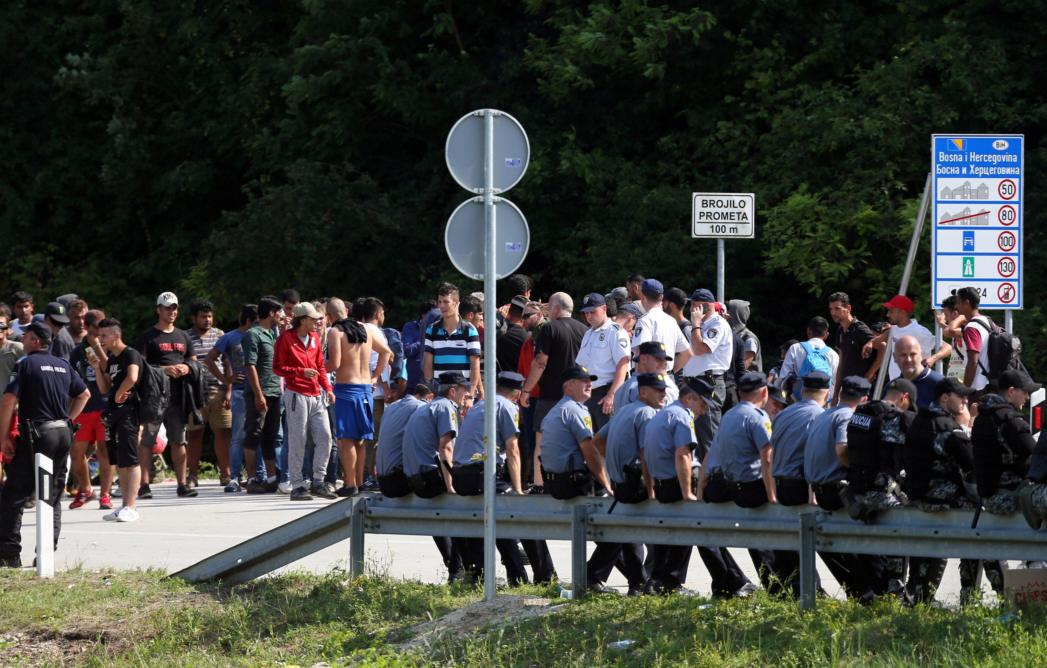 FILE PHOTO: Migrants and Bosnian police eye one another in Velika Kladusa, Bosnia, near the border with Croatia