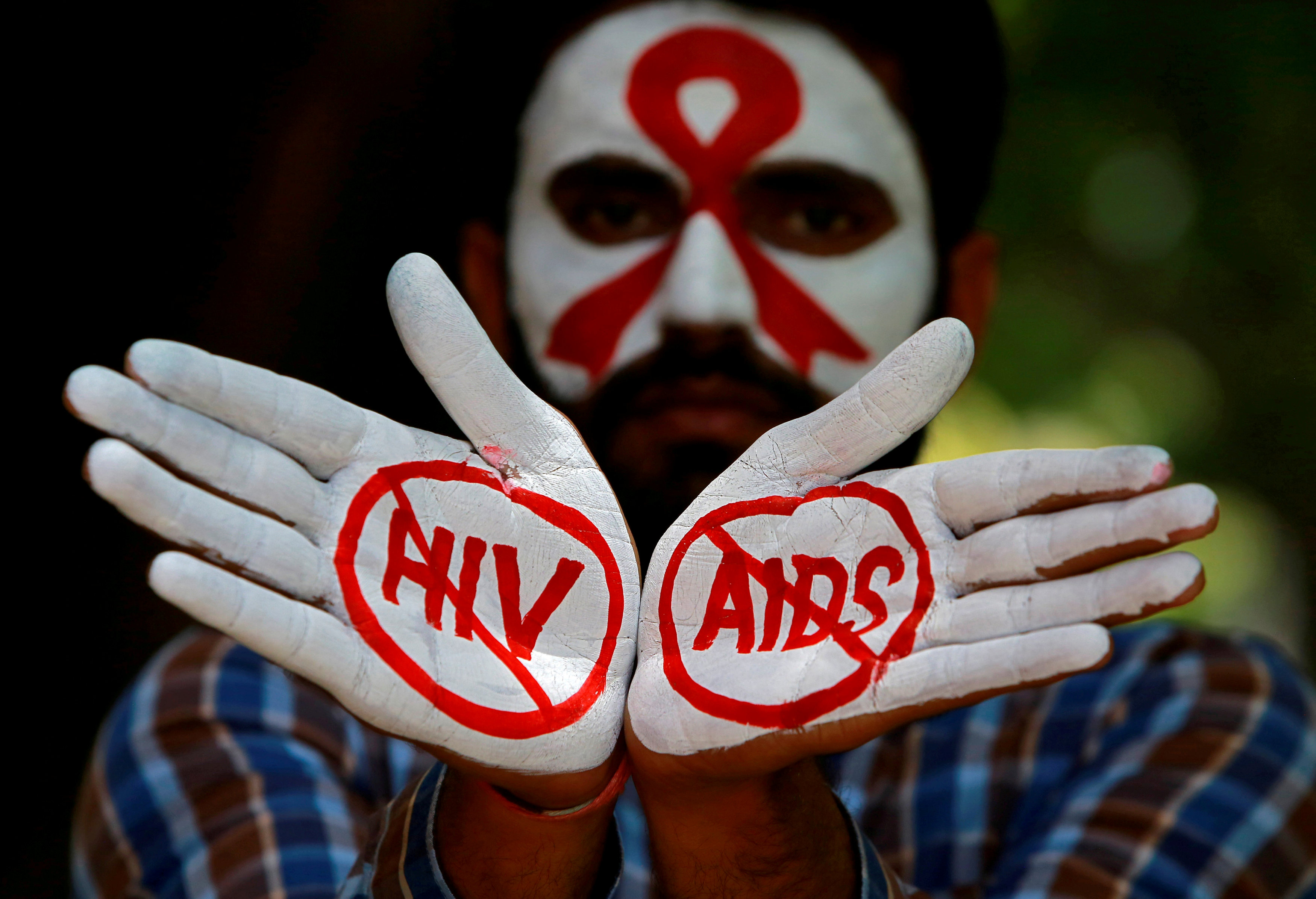 FILE PHOTO: A student displays his hands painted with messages as he poses during an HIV/AIDS awareness campaign to mark the International AIDS Candlelight Memorial, in Chandigarh