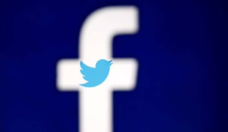 A 3D-printed Facebook logo is displayed in front of the Twitter logo, in this illustration