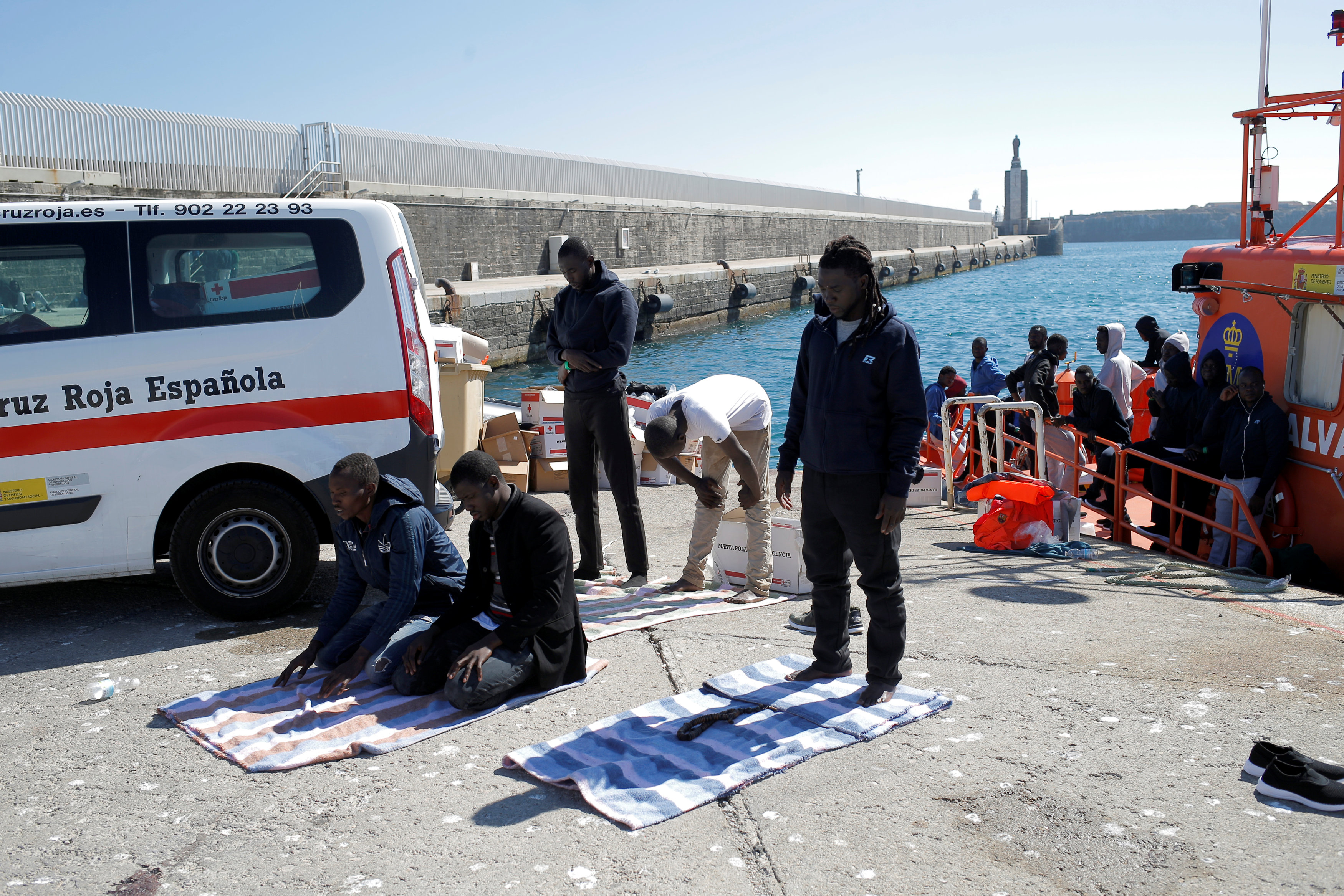 Migrants pray after arriving on a rescue boat at the port of Tarifa