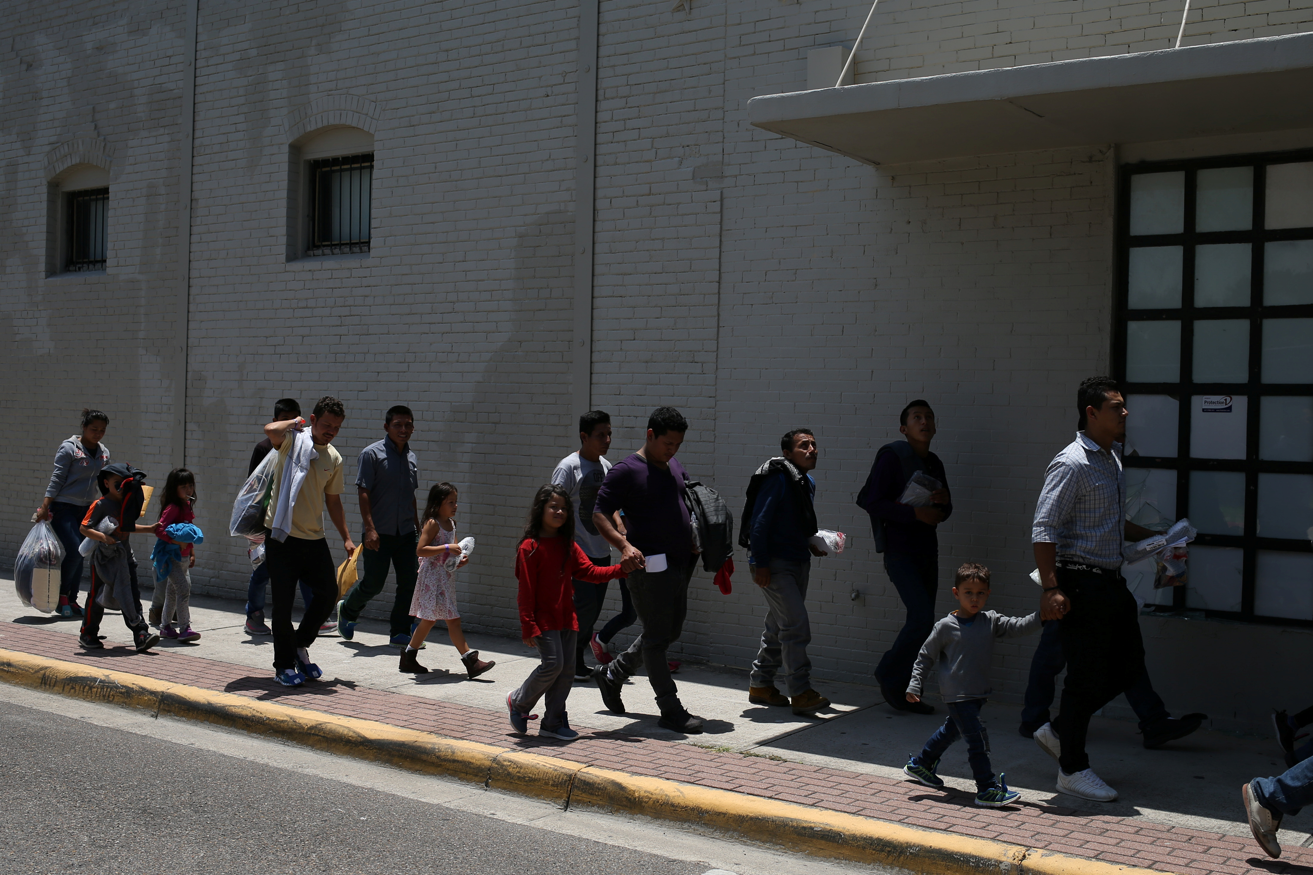 Undocumented immigrant families walk from a bus depot to a respite center after being released from detention in McAllen