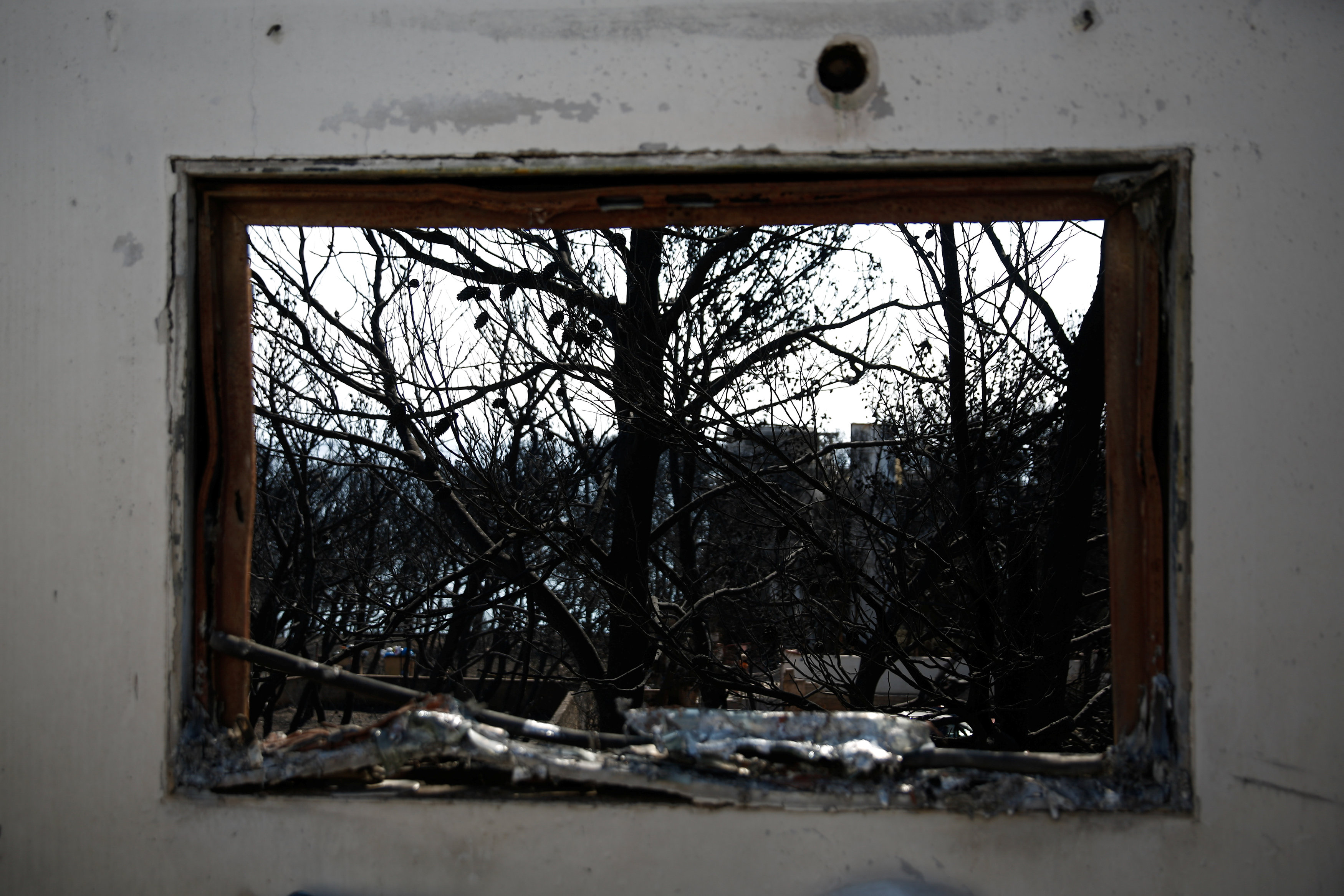 Burnt trees are seen through a window of a destroyed house following a wildfire in the village of Mati, near Athens