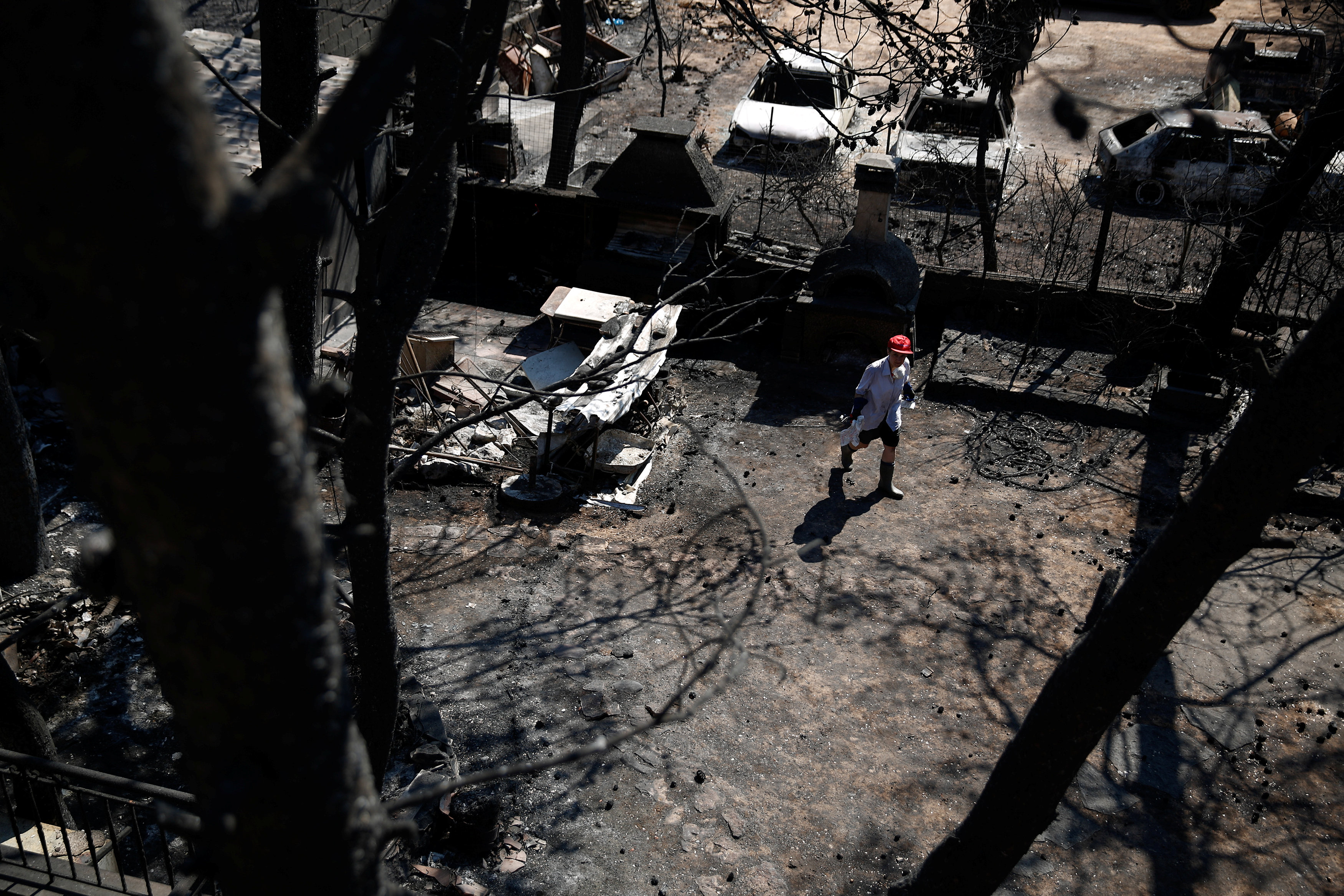 A woman makes her way in the yard of her house following a wildfire in the village of Mati, near Athens