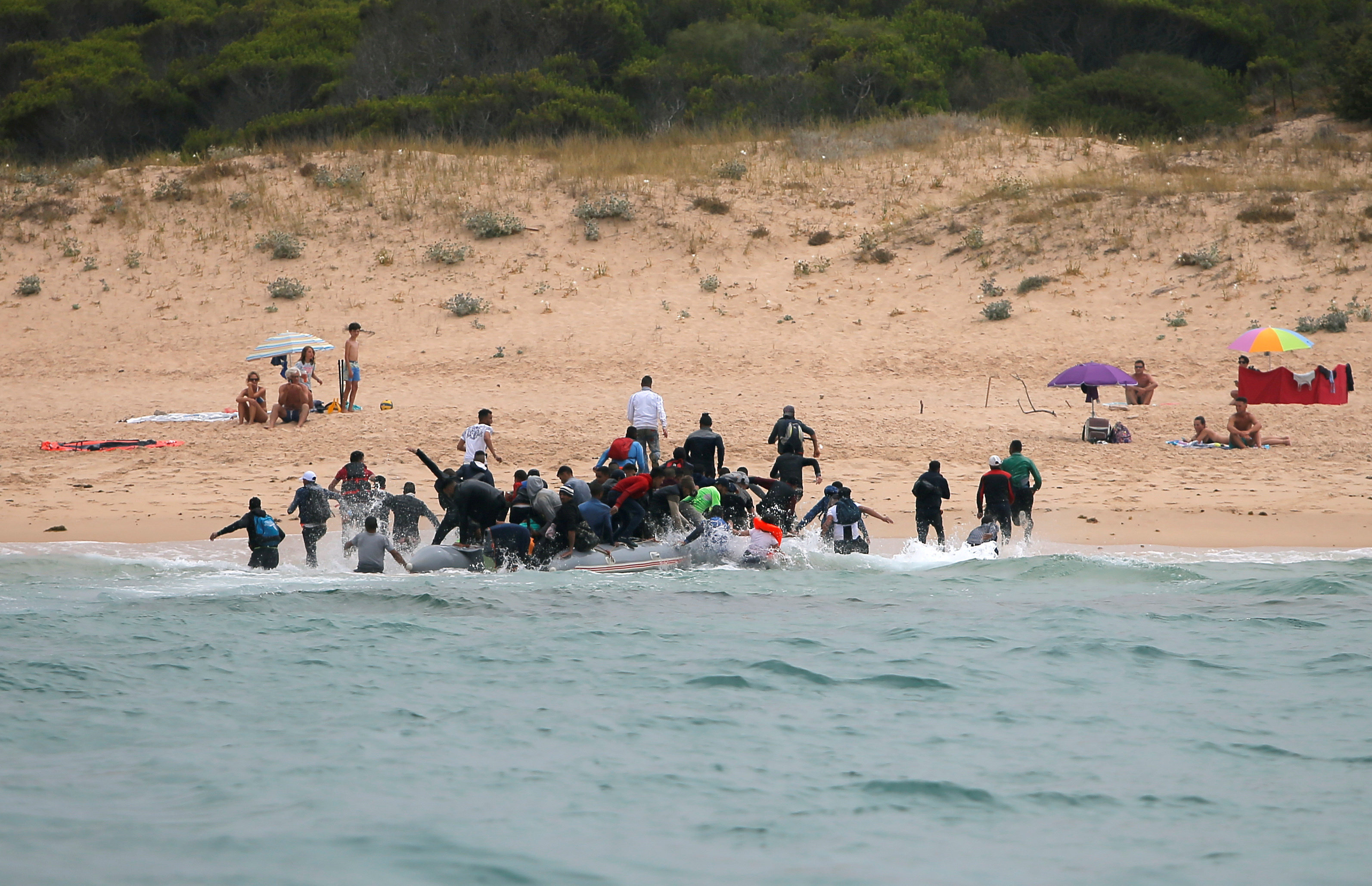 "Moroccan migrants disembark from a dinghy at ""Del Canuelo"" beach after they crossed the Strait of Gibraltar sailing from the coast of Morocco, in Tarifa"