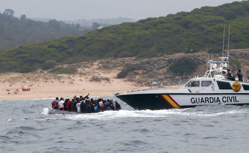 "Spanish civil guards try to stop to moroccan migrants before disembarking from a dinghy at ""Del Canuelo"" beach after they crossed the Strait of Gibraltar sailing from the coast of Morocco, in Tarifa"