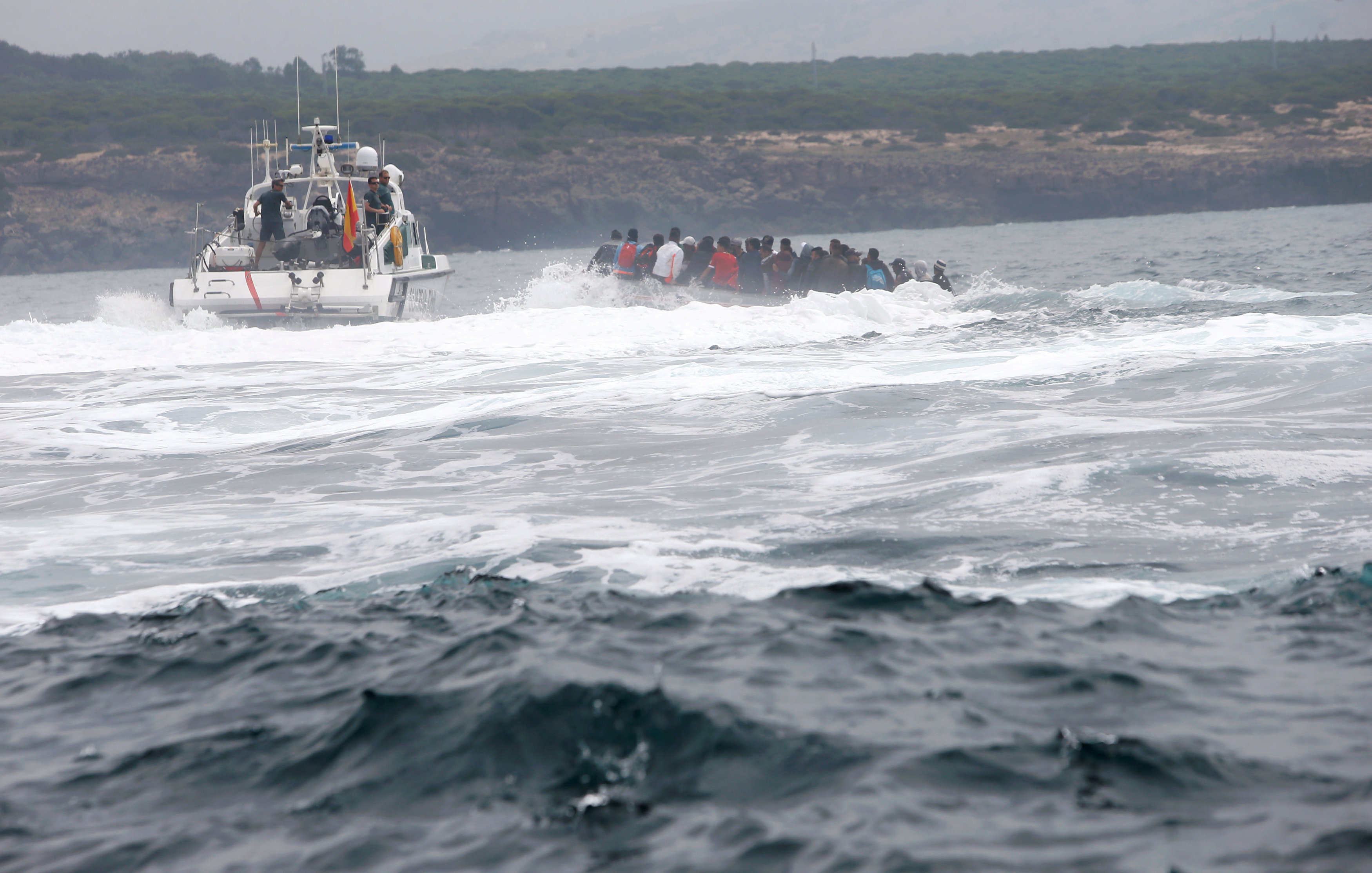 "Spanish civil guards try to stop to migrants before disembarking from a dinghy at ""Del Canuelo"" beach after they crossed the Strait of Gibraltar sailing from the coast of Morocco, in Tarifa"