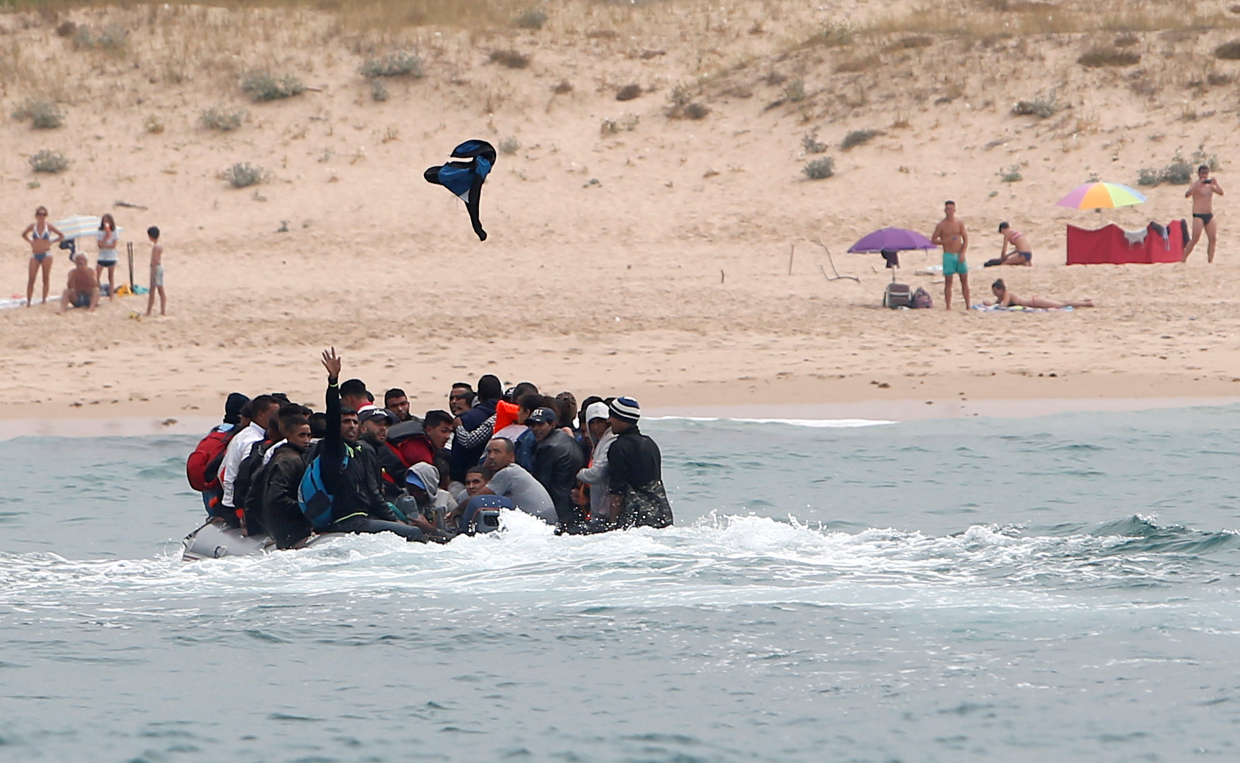 "Migrants are seen before disembarking from a dinghy at ""Del Canuelo"" beach after they crossed the Strait of Gibraltar sailing from the coast of Morocco"