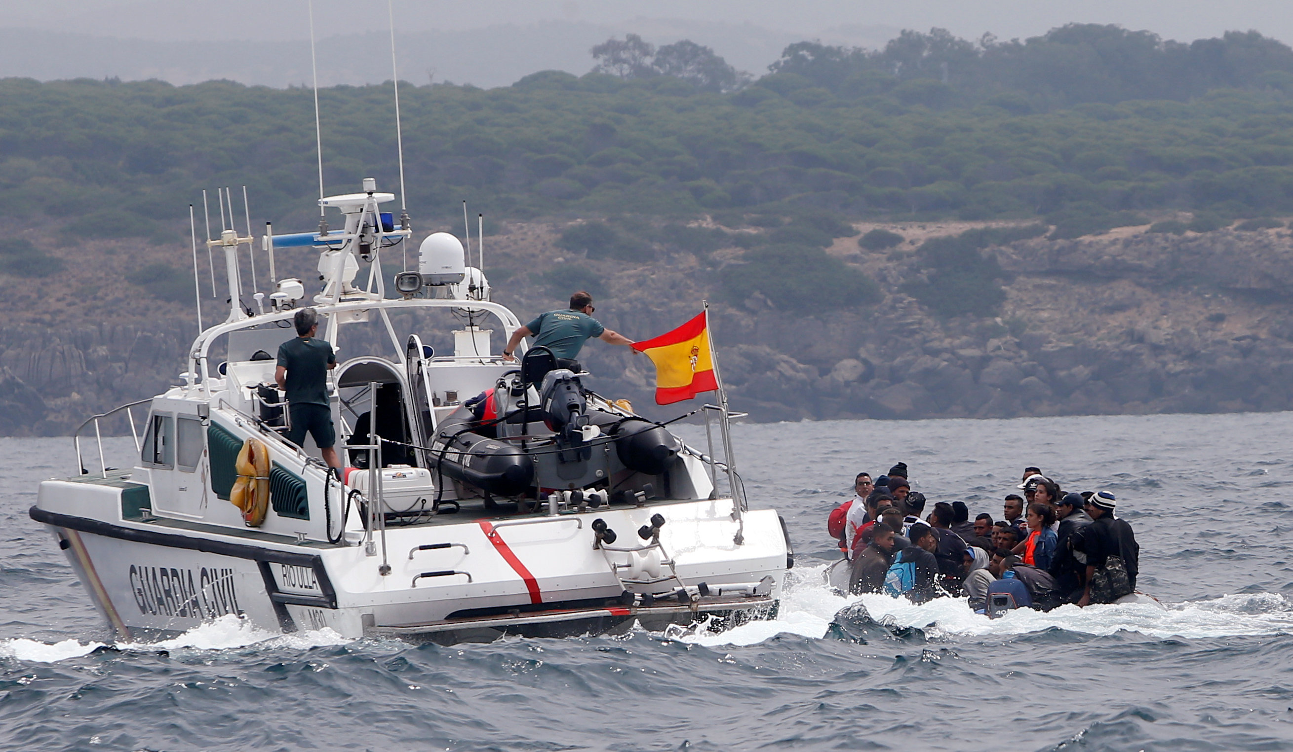 "Spanish Civil Guards try to stop migrants before disembarking from a dinghy at ""Del Canuelo"" beach after they crossed the Strait of Gibraltar sailing from the coast of Morocco, in Tarifa"