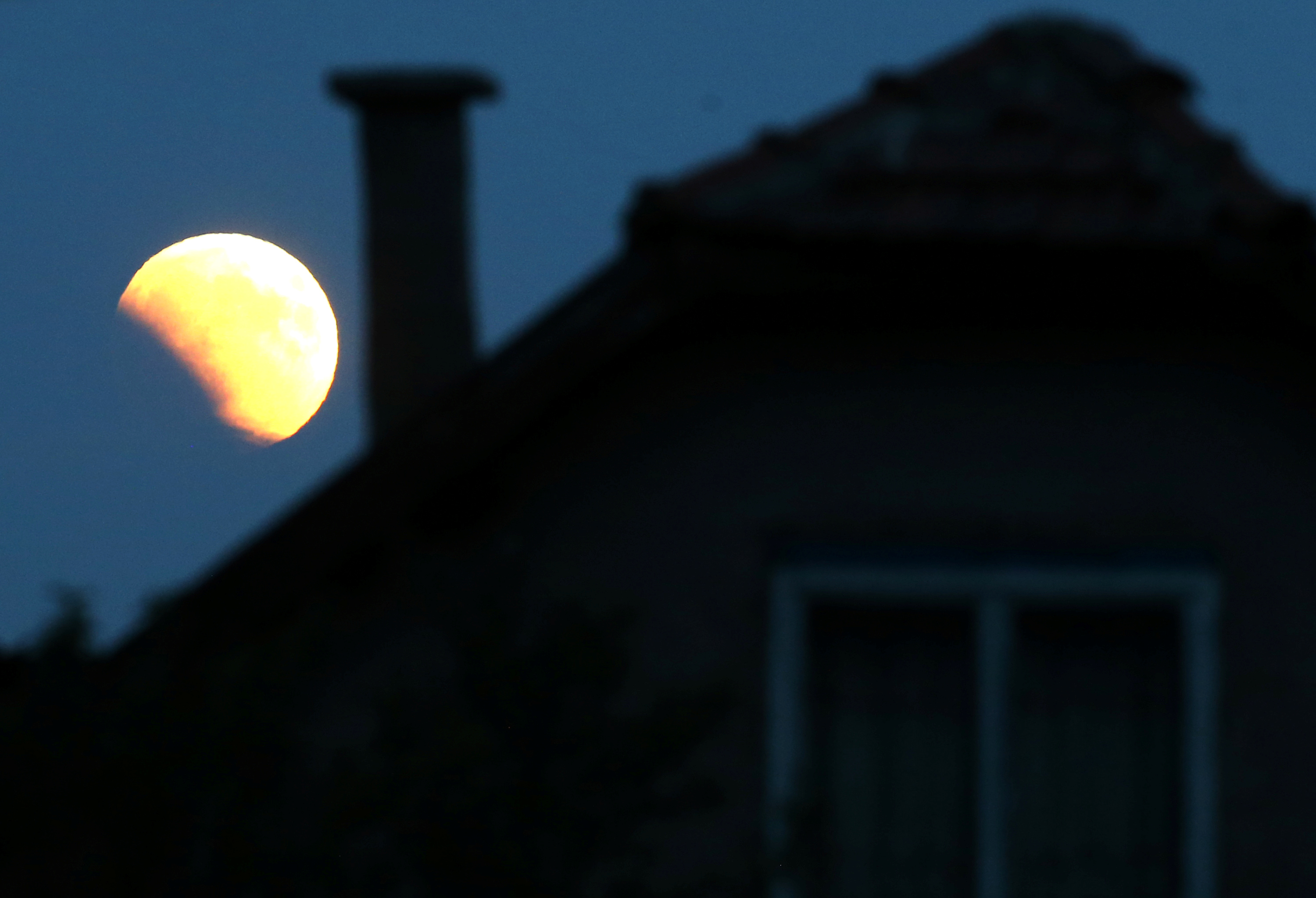 Full moon during eclipse rises behind house in Zenica