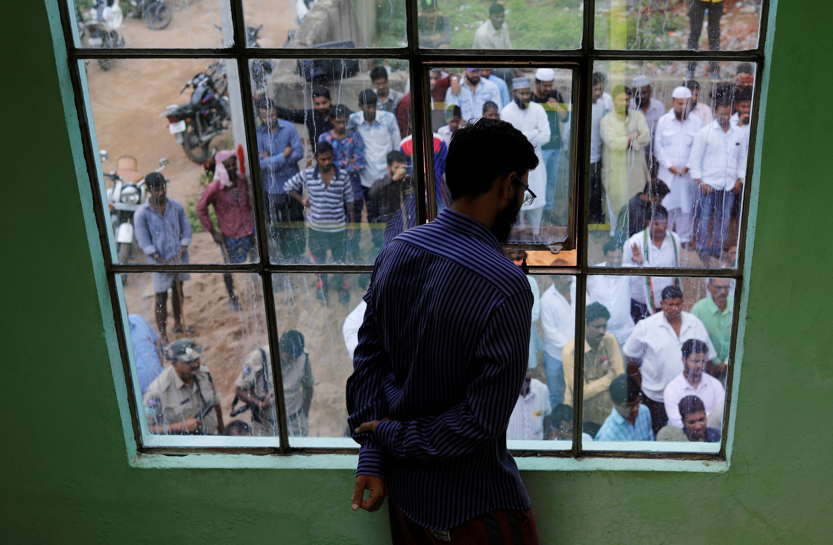 Mohammed Aslam, brother of Mohammed Azam, who was lynched by a mob, looks out of his house as people gather to give their condolences to the family in Hyderabad