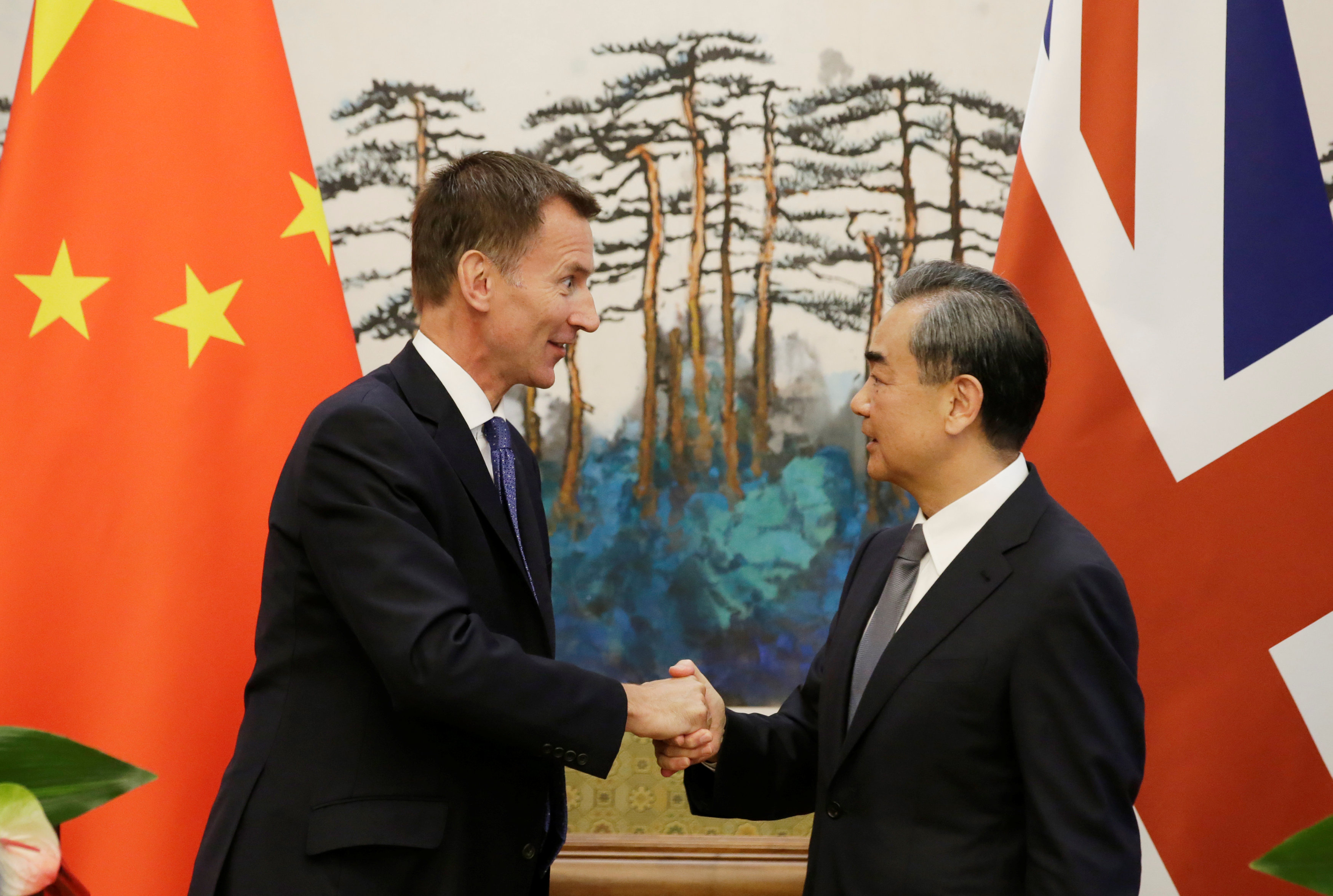 Britain's Foreign Secretary Jeremy Hunt shakes hands with China's Foreign Minister Wang Yi in Beijing