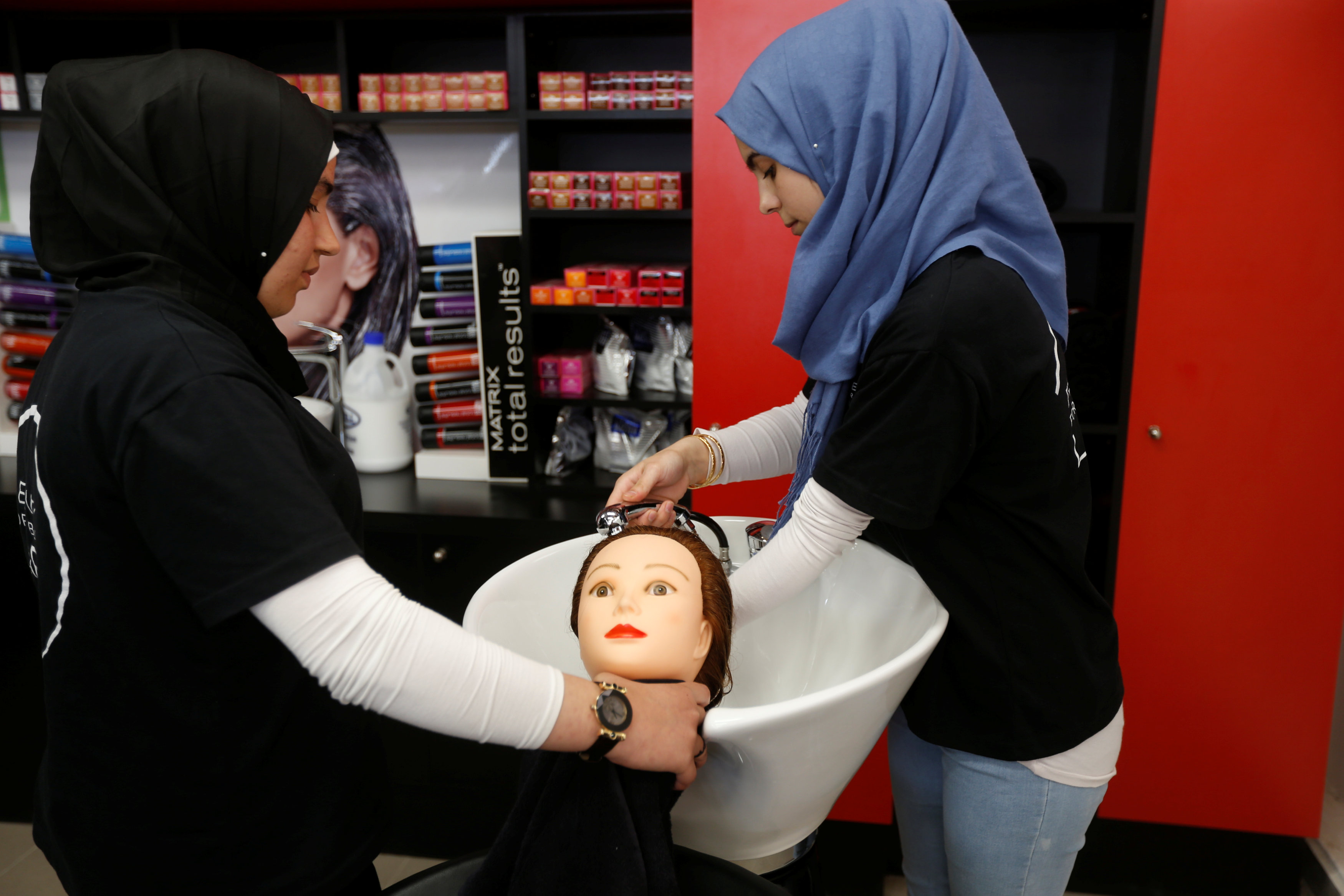 Nour, a Syrian refugee practices on hair mannequins at a training salon in Bar Elias