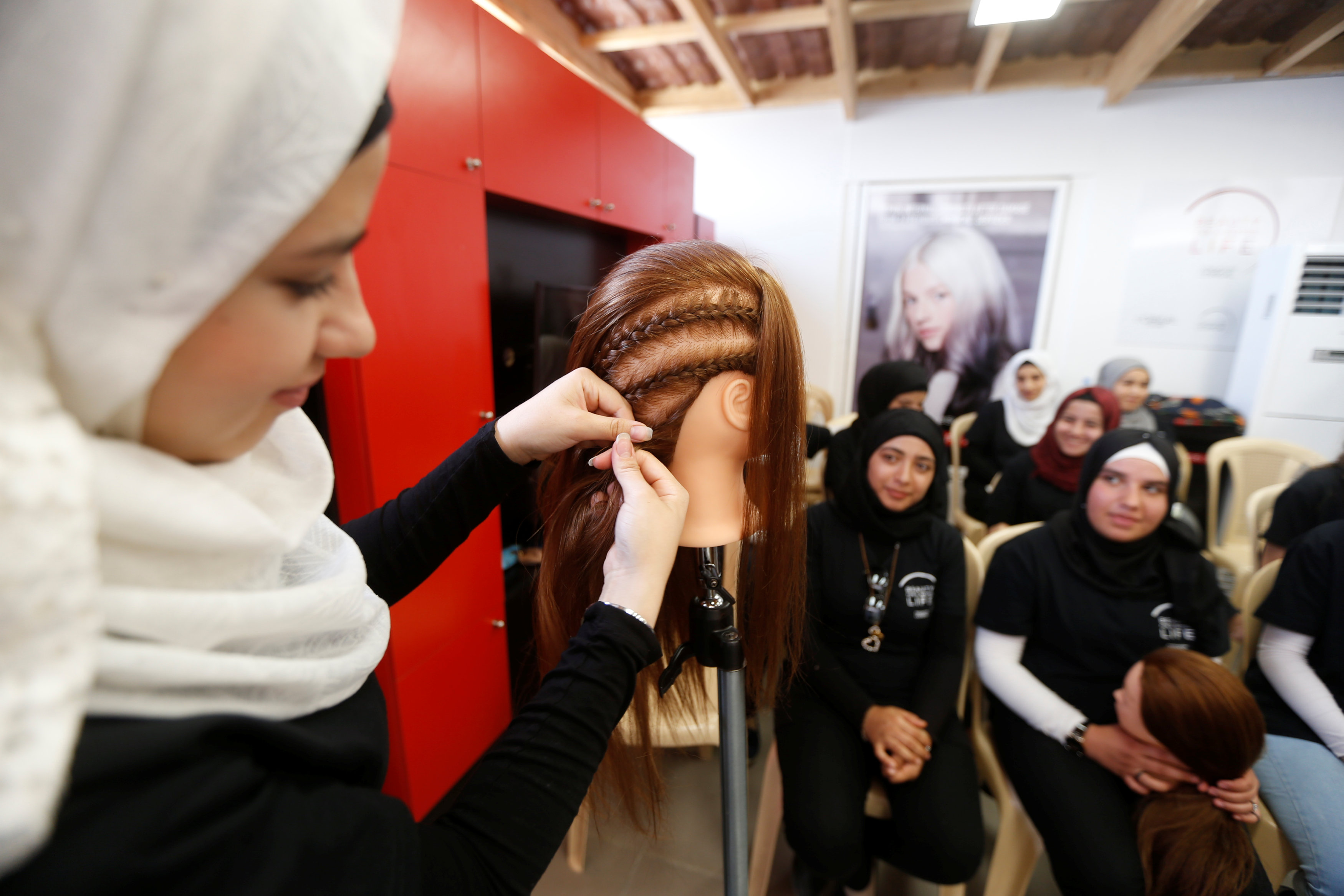 A woman practices on hair mannequins at a training salon in Bar Elias