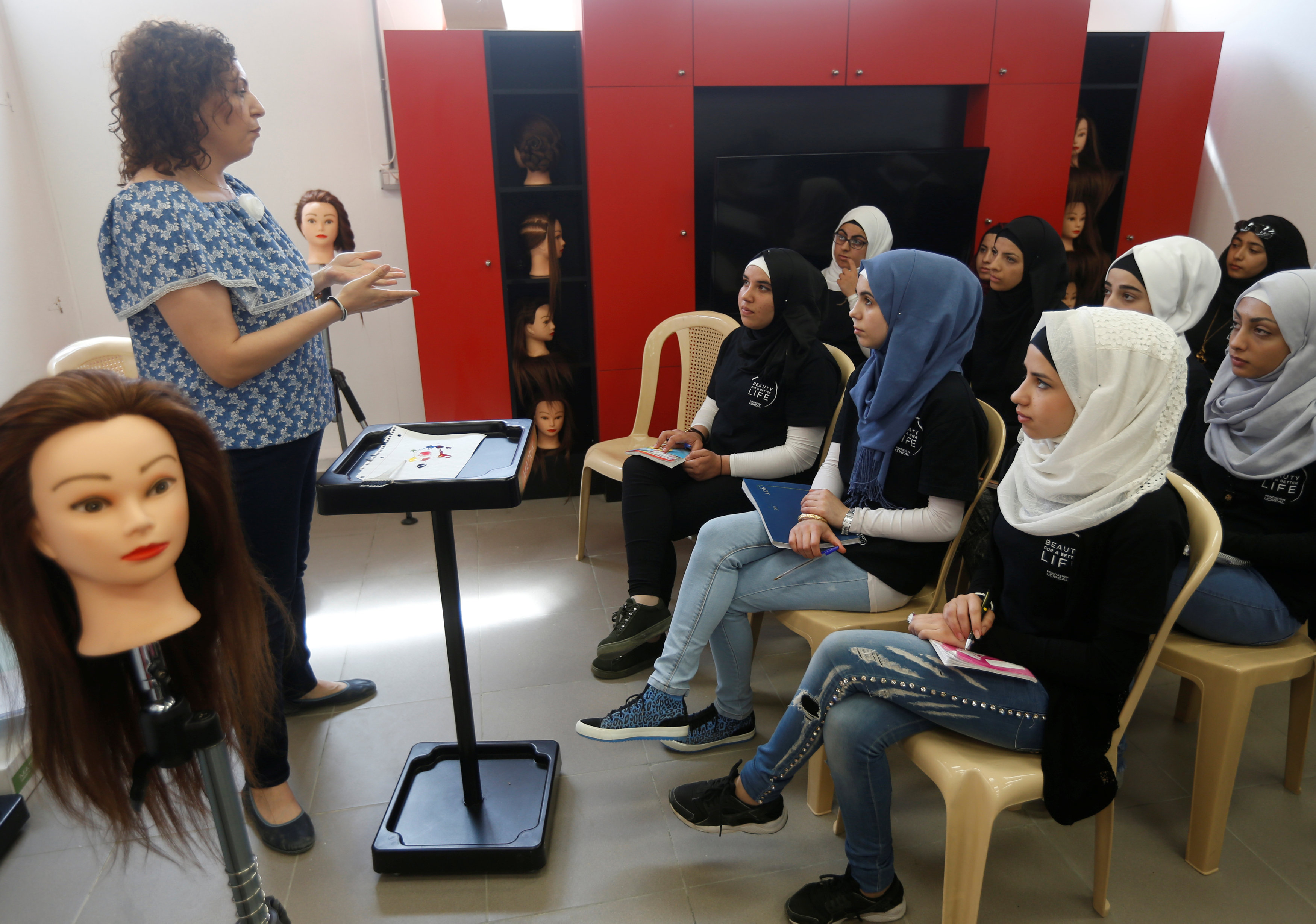 The women's hairdressing instructor gestures as she talks at a training salon in Bar Elias