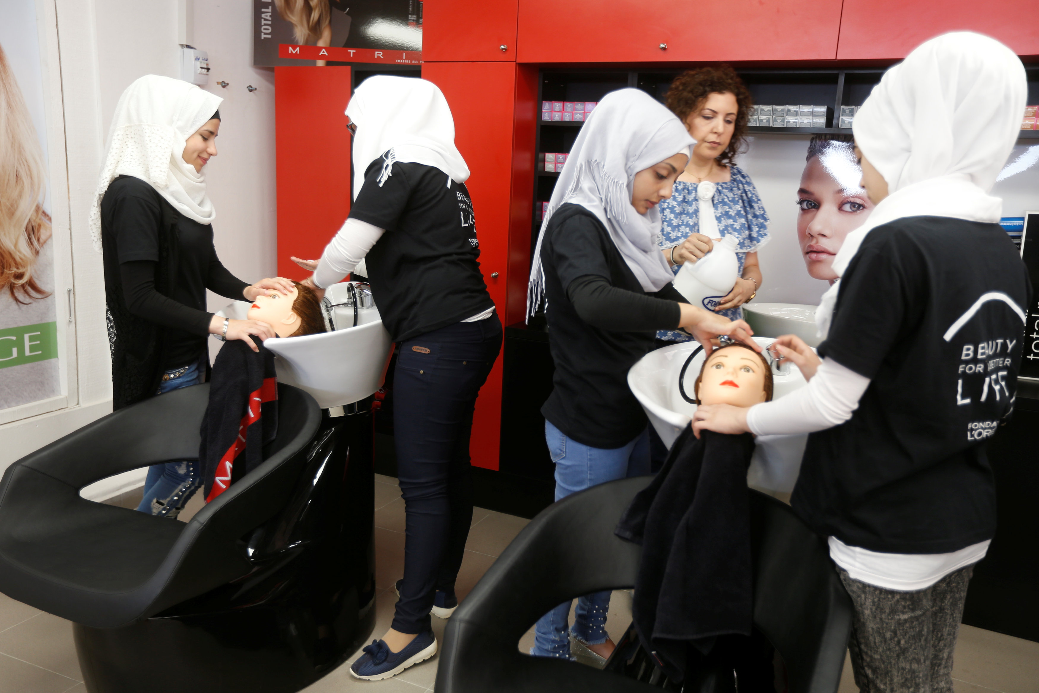 Women practice on hair mannequins at a training salon in Bar Elias