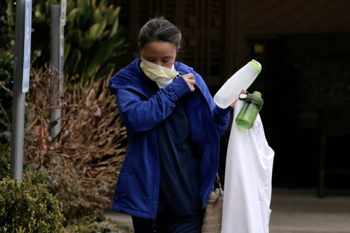 FILE PHOTO: A worker removes her mask upon leaving the Life Care Center of Kirkland in Washington