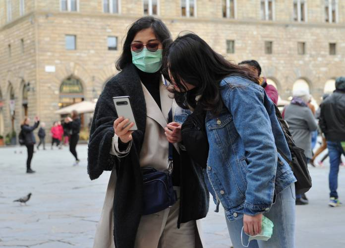 People wearing protective masks look at a phone as Italy battles a coronavirus outbreak, in Florence