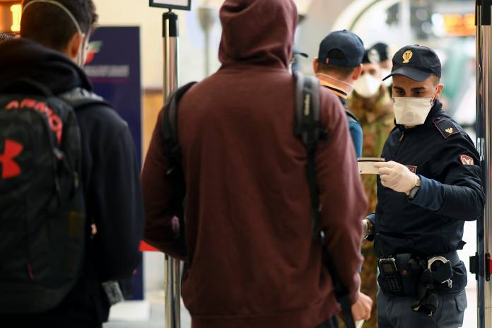 Police officers make checks on people at Milan's main train station