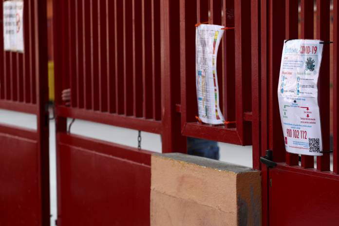 A worker closes the entrance of a school in Madrid