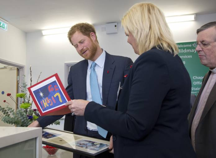 Britain's Prince Harry is presented with a Christmas card and framed photographs of Princess Diana during her visit to the hospital, by Kerry Reeves-Kneip, Director of Fundraising during a visit to Mildmay HIV hospital and charity in London