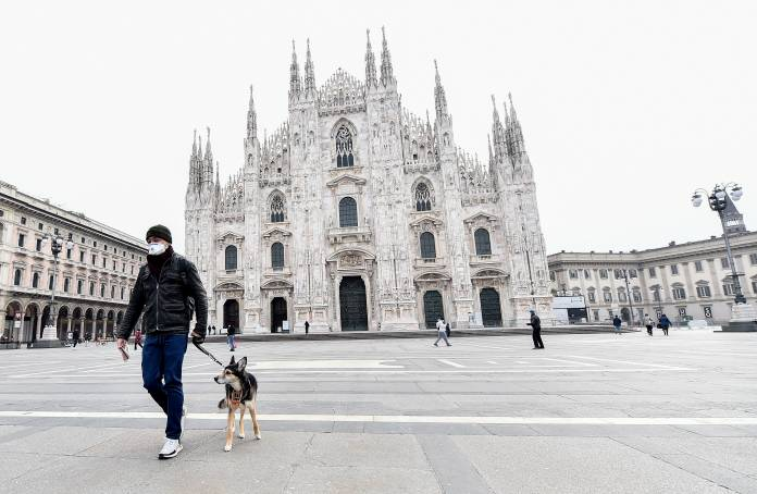 A man wearing a protective face mask walks a dog in Duomo square after a decree orders for the whole of Italy to be on lockdown in an unprecedented clampdown aimed at beating the coronavirus, in Milan