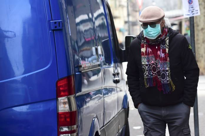 A man with a protective mask walks in Madama Cristina market in Turin
