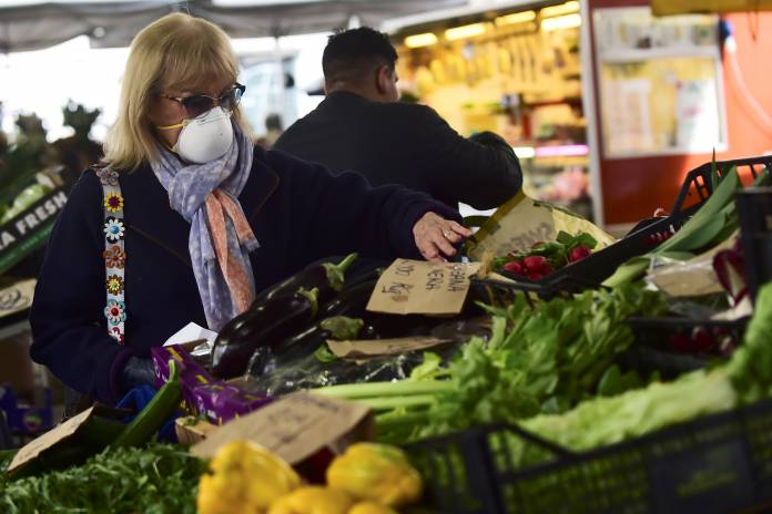 A woman with a protective mask checks vegetable prices at Madama Cristina market in Turin