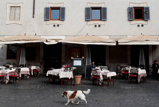 A dog passes in front of an almost empty restaurant in Trastevere area, after a decree orders for the whole of Italy to be on lockdown in an unprecedented clampdown aimed at beating the coronavirus,in Rome