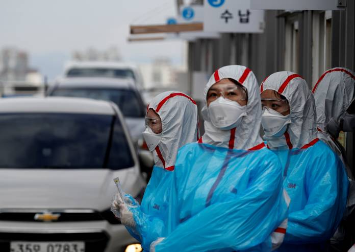 FILE PHOTO: Medical staff in protective gear work at a 'drive-thru' testing center for the novel coronavirus disease of COVID-19 in Yeungnam University Medical Center in Daegu
