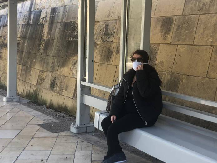 woman wearing a mask on a bus stop