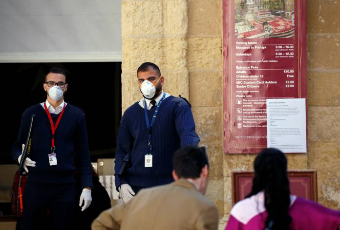 Security staff wearing protective face masks and gloves wait for visitors in Valletta