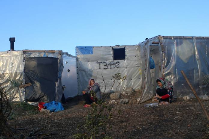 FILE PHOTO: Women sit next to tents, at a makeshift camp for refugees and migrants next to the Moria camp, on the island of Lesbos
