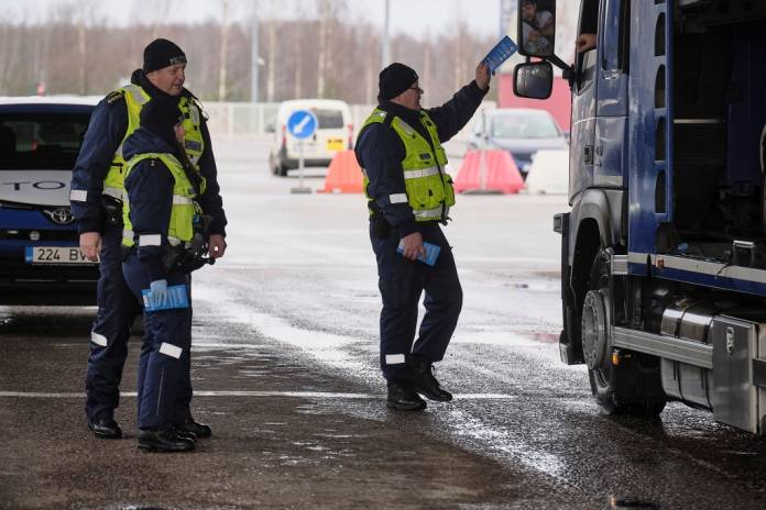 Estonian police officer Urmas Neihaus gives a leaflet with information about coronavirus disease (COVID-19) to a person entering Estonia at the border crossing point with Latvia in Ikla, Estonia March 13, 2020. REUTERS/Ints Kalnins