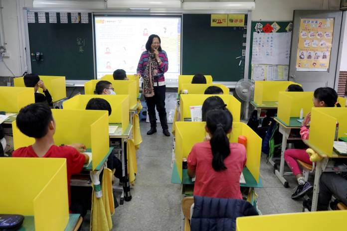 Pupils sit in desks with yellow dividers at Dajia Elementary school in Taipei