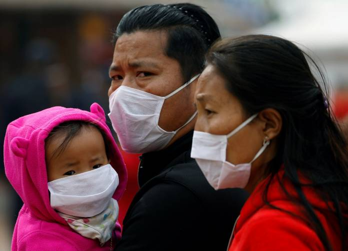People wearing face masks amid concerns about the spread of coronavirus disease (COVID-19) outbreak are pictured at the premises of Boudhanath Stupa in Kathmandu