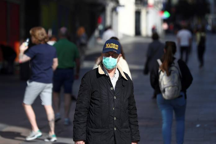 Man, wearing a protective mask, walks through an empty street in Madrid