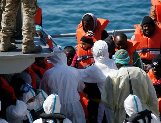 Police officers in protective clothing against possible coronavirus infection tag a child migrant on a military ship after arriving in Senglea