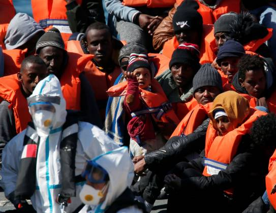 A child migrant gestures as Armed Forces of Malta soldiers in protective clothing against possible coronavirus infection stand near rescued migrants on a military ship after arriving in Senglea